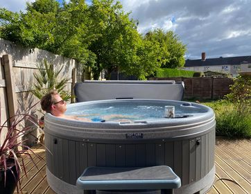 Customer in Orbis hot tub with cup of tea